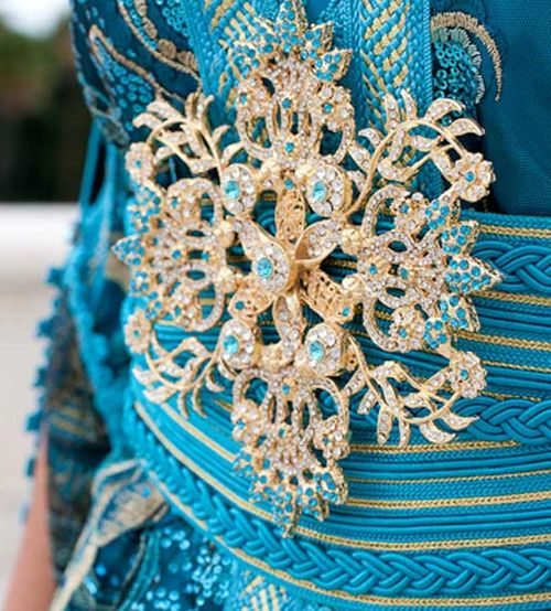 """a good close up of the twisted silk of the belts and and sfifa braid edging of a Moroccan tkchita. The silk floss is twisted using an electric fishing tackle which twists into ropes that are wound on a spindle to be woven or braided, then stitched by hand onto the material. The metal is a """"shouka"""" pinned onto the belt."""