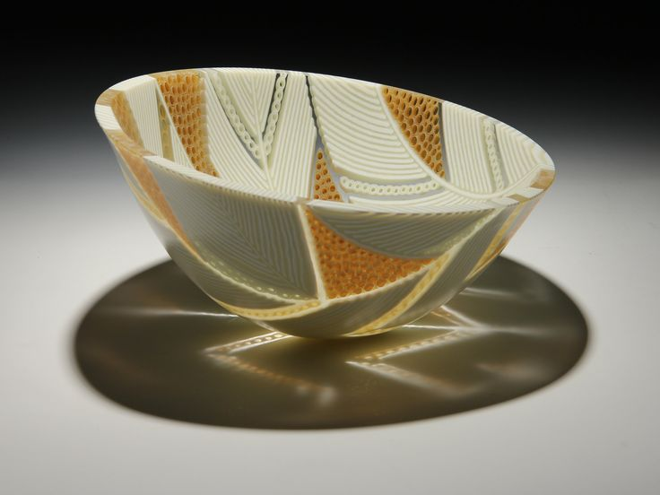 Arrows Bowl in Honey and Cream by Patti & Dave Hegland. Featuring an intricate angular design of cream-colored glass placed on edge, this sculptural piece incorporates segments of hand-pulled murrini in cream, ambers, and clear to form a balanced vessel. The detail is enhanced by the vessel's satin interior. The strong geometry and structure of this work is inherent in the strip construction approach used to create it. Large sheets of glass are cut into narrow strips, laid on edge, a...