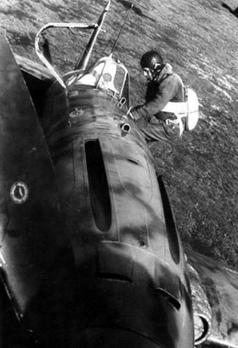 """An Italian fighter pilot, in complete flight suit boarding on a Macchi MC.202 """"Folgore"""". The photo highlight the arrangement of principal armament of this famous Italian fighter: two 12,7mm Breda-Safat synchronized with the propeller, each with 360 rounds over the engine cowling. The airplane is also equipped with the anti-sand filter on the left side of cowling."""