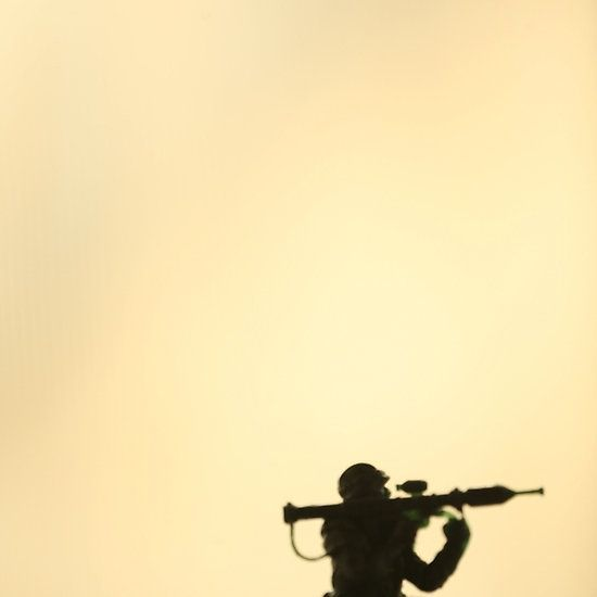 Silhouette of toy soldier firing gun. Color digital artistic photograph by Edward Olive commercial portrait photographer from Madrid Spain.