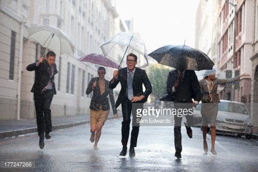 Stock Photo : Business people with umbrellas running in rainy street