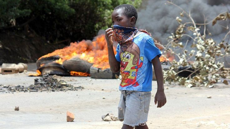 A child covers his mouth in Lusaka's Kanyama Township as he walks past a burning barricade of tyres on January 12, 2018, during clashes with protesters demonstrating against a curfew and a ban on street commerce imposed by the government in the wake of a cholera outbreak. Police in Zambia clashed on January 12 with residents in the capital Lusaka protesting an official ban on street commerce in a poor suburb intended to tackle a deadly cholera outbreak.