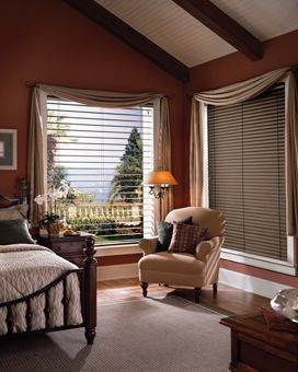 """Hunter Douglas Reveal with MagnaView aluminum blinds. When you desire a view when the blinds are down, but not closed, these modern metal blinds allow the slats to next together, allowing 2x the view you would have with a standard 2"""" blind. Specialty shapes, orientations and colors available. This is a wonderful bedroom idea for privacy and room darkening options. Note the beautiful drapery swags over the window treatments in this bedroom."""