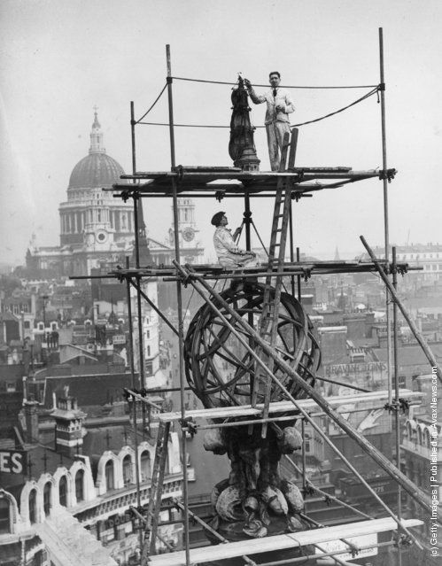 Workmen cleaning the copper globe and galleon which stand on the roof of Cook's Building in London's Ludgate Circus. St Paul's Cathedral is clearly visible in the background. (Photo by Harry Todd/Fox Photos/Getty Images). 21st April 1939