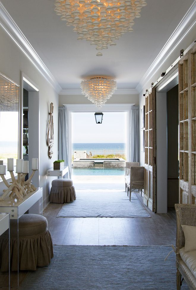 Beach house interiors. Beach house interior ideas. The best decor of all is the view to the ocean. The hand poured porcelain cup chandeliers were imported from UK. Paint Color: Sherwin Williams Reposed Gray at 50% strength. #BeachHouse #Interiors Heritage Homes of Jacksonville. Villa Decor & Design.