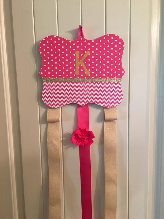 Initial bow and Headband Holder! Perfect for that special girls room! This barrette holder is a fuchsia pink polka dot and chevron pattern with a gold glitter band. It comes with 3 strands of ribbon to hold barrettes and 2 loops to hold standard headbands . Two gold and one fuchsia