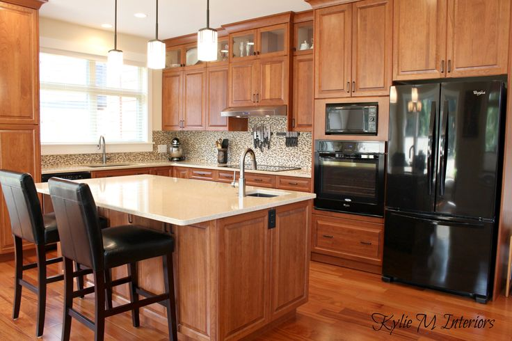 cherry kitchen cabinets in modern transitional kitchen with crema quartz countertops, black appliances and exotic wood flooriong with small mosaic tile backsplash