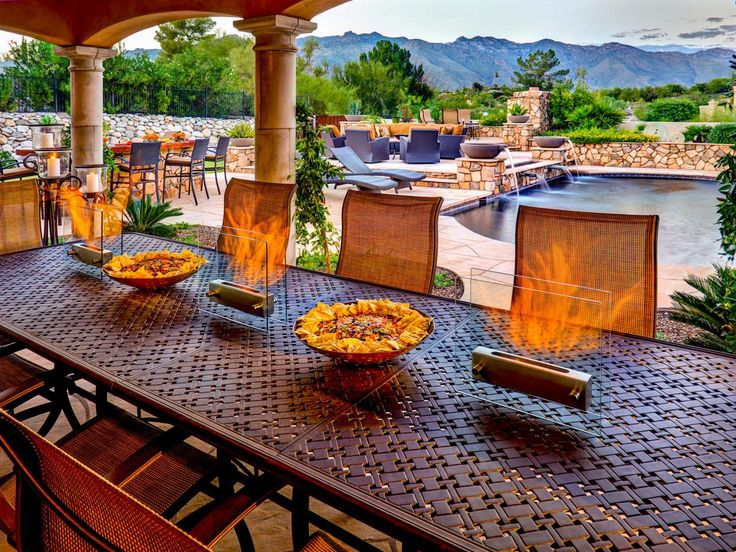 This Mediterranean alfresco dining room with tabletop fireplaces includes a gorgeous view of the stone patio and refreshing pool. This dining table is a perfect place to relax and enjoy the beautiful outdoor space.