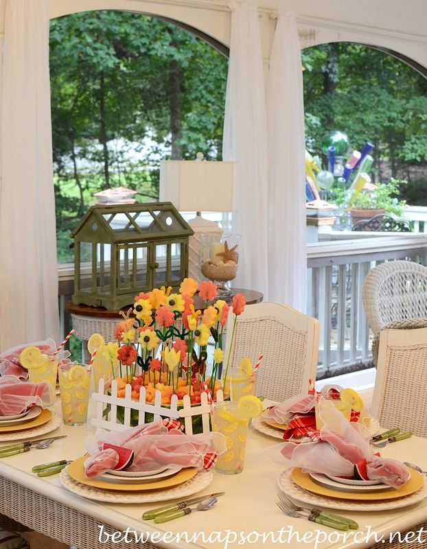 Summer Table Setting with a Carved Watermelon Centerpiece 2a--fruit flowers set in a watermelon with a popsicle stick white fence.