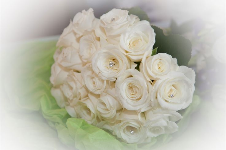 A white rose bouquet with diamond pins.