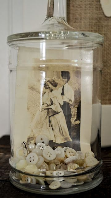 Cute idea for old photos, place inside a glass canister with vintage items like old buttons, old keys, jewelry, etc.