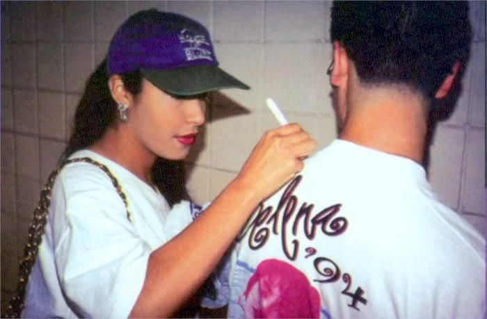 Selena autographing a fans shirt..the last t-shirt she designed
