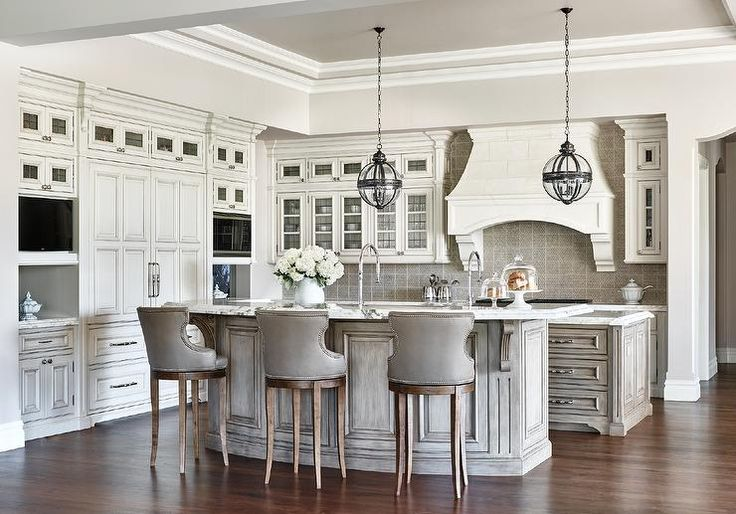 Glamorous, well appointed kitchen features Restoration Hardware Victorian Hotel Pendants hung from a light gray tray ceiling over a curved gray wash breakfast bar topped with gray and white marble beveled countertops seating three gray leather counter stools facing a second island with both islands fitted with sinks and polished nickel gooseneck faucets.