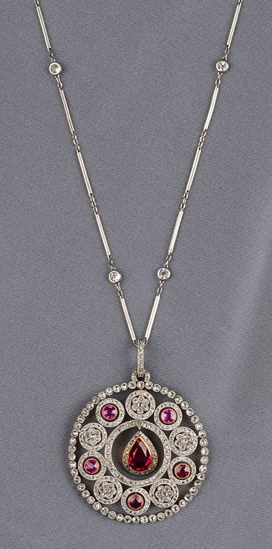 Edwardian Synthetic Ruby, Ruby, and Diamond Pendant, Retailed by Koch, centering a pear-shaped synthetic ruby measuring approx. 9.00 x 5.40 x 3.90 mm, set in a flexible mount framed by rose-cut diamond melee, further set with circular-cut rubies and rose-cut diamond melee, millegrain accents, platinum-topped gold mount, suspended from a platinum delicate baton link chain, spaced by old European-cut diamonds, approx. total diamond wt. 2.10 cts., lg. 2, 16 in., within a signed fitted box.