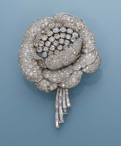 A DIAMOND FLOWER BROOCH   Designed as an open rose pavé-set with baguette, single and old-cut diamonds, circa 1935, 8.5 cm long