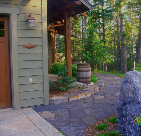 Beautiful flagstone pathway wraps around the front of the house to the front door, rustic look.