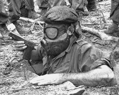 "John Olson. Cu Chi, South Vietnam, November, 1967: Colt .45 and flashlight in hand, wearing a gas mask, ""tunnel rat"" Sp4 Richard Winters of 2nd Battalion, 27th Infantry, 25th Infantry Division cautiously lowers himself into a 1,000-foot-long Viet Cong tunnel found in Vietnam's ""Iron Triangle."""