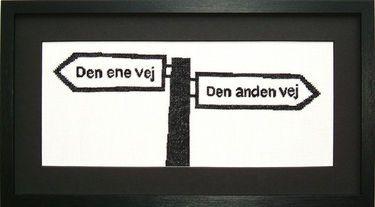 15-70-0316 Broderipakning - Billede - Den ene vej  Fru Zippe - design Anni Gamborg   Str. 12,5 x 30 cm.   Broderes med korssting på hørlærred bleget 10.5 tråde pr cm. efter sort/hvidt tællemønster.    Pakningen indeholder billede, stof, mønster og blomstret bomuld garn samt en nål Rammen medfølger ikke.