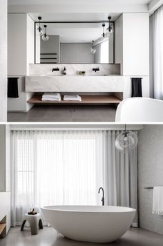 In this master bathroom, the vanity has dual sinks, a large black framed mirror and a standalone soaker bathtub.