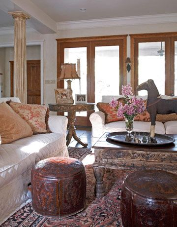 A pair of slipcovered Lee sofas, along with leather hassocks from the Arrangement in Dallas, furnish the Boltons' new living room; on the coffee table stands a classic Bolton detail, a vintage toy horse made from papier-mâché and horsehair.   - CountryLiving.com