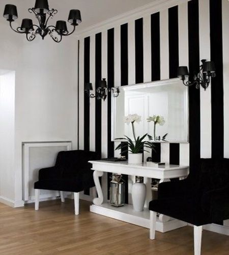 A black and white entrance hall features a bold striped wall that allows the furniture and accessories to pop. Vertical stripes are a simple way to visually heighten a room, so if you have a low ceiling think about adding some stripes. You don't have to go black and white and can choose your own colours to match the existing hues in a room.