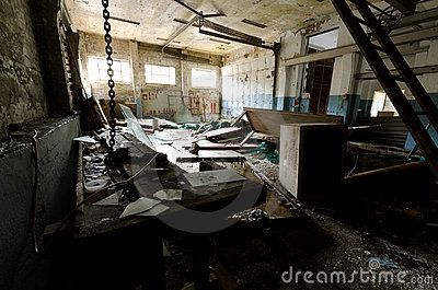 Inside view of an abandoned machine shop with debris and damaged equipment in Ivittuut Greenland
