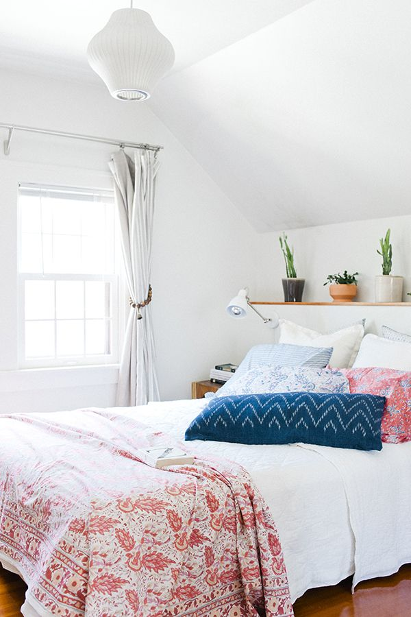 White bedroom with lots of colorful pillows and throw