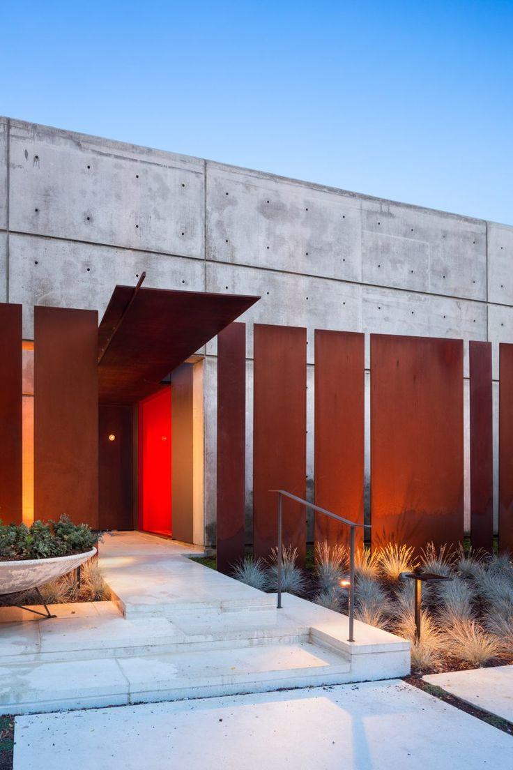 The front facade of this family home in Tennessee by Hastings Architectural Associates comprises a monolithic concrete wall and weathering steel panels