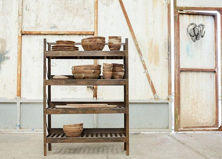 A patinated finish gives the UMI iron shelf from Nkuku an industrial look and feel. Four slatted shelves provide easy storage for pots, pans or plants.