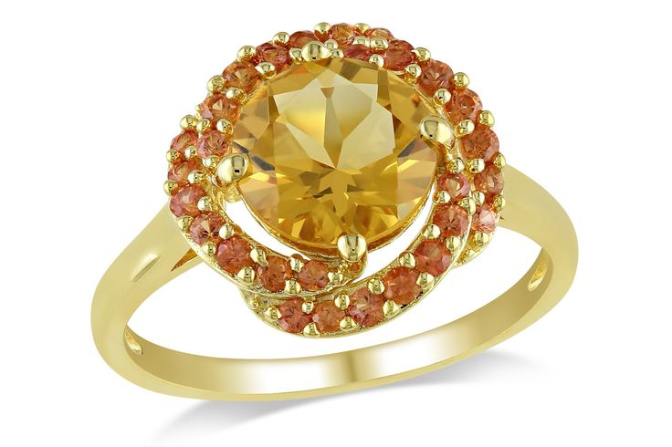 Look no further than this timelessly elegant ring for a study in fashion glamour. Although the yellow rhodium plated over sterling silver encrusted shape band is beautiful, the real highlight of this ring is the round center citrine gemstone and its sounding with orange sapphires: Taking your eyes off of it will prove impossible!