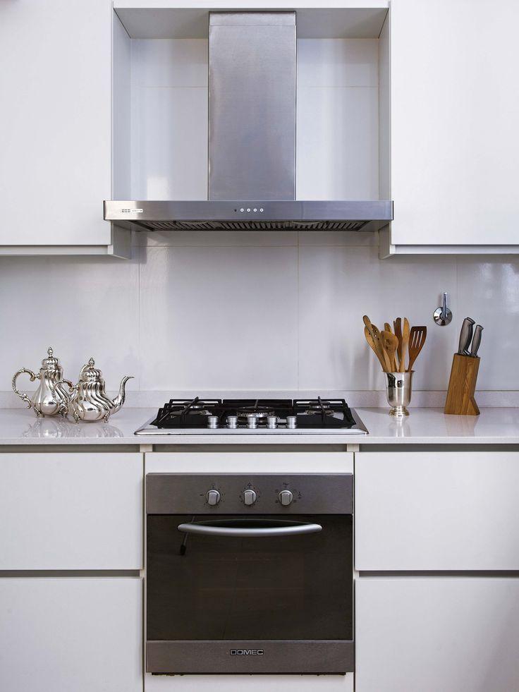 Cocina a puro blanco con detalles plateados en un depto en el Palacio Estrugamou de Buenos Aires.