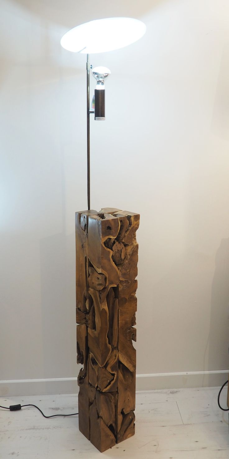 This square root spotlight has a contemporary look with its metal detail. It's neat square shape allows this model to fit in any corner of the home. It's light will shine beautifully on the teak root lamp base below creating a stunning effect. Made from teak root.Available in two sizes.