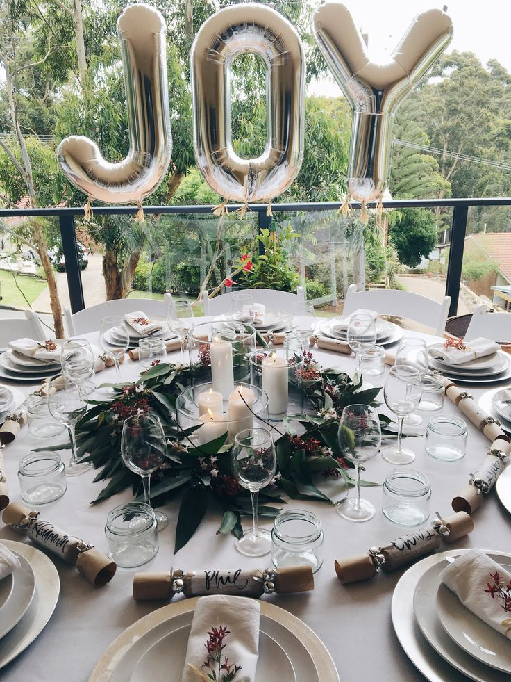 JOY to the world! What would a party be without foil letter balloons? Australian Christmas table arrangement. Styled with a native flower garland made using eucalyptus leaves, Christmas Bush and Jasmine and handmade Christmas crackers in lieu of place cards.