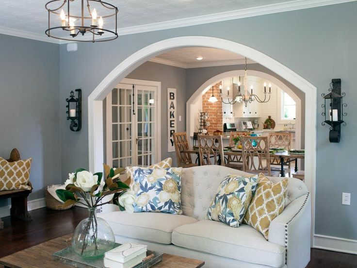 The wall dividing the living and dining rooms is opened up with a wide archway for a more open feel. The distinctive patterned ceiling tiles were retained but new recessed lighting and fixtures were added.