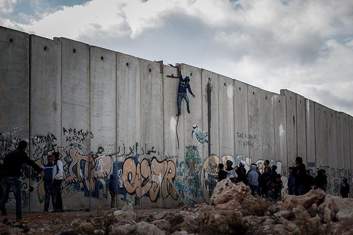 November 2013. Palestinian protesters try to climb the Israeli separation barrier during clashes at the Qalandia checkpoint following the funeral of a young Palestinian. Photograph: Federico Scoppa/Corbis