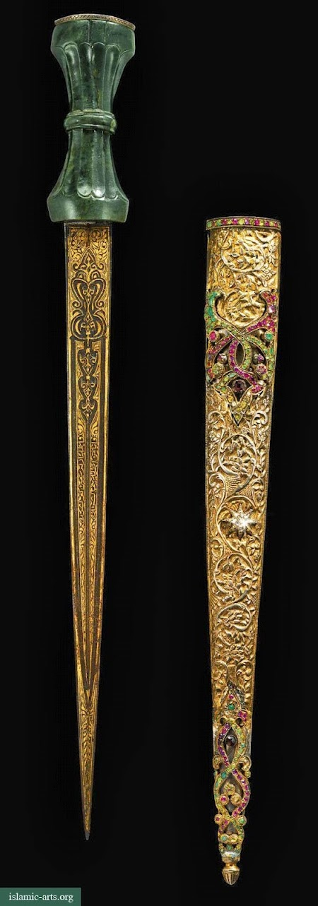 AN OTTOMAN JADE-HILTED AND GEM-SET DAGGER AND SCABBARD, TURKEY, 19TH CENTURY.  The straight steel blade with central ridge, wholly decorated with gold gilt inscriptions and varied motifs, the waisted dark-green jade hilt with carved flutes, the pommel embellished with openwork silver set with gemstones, the engraved silver scabbard adorned with cabochon and faceted gemstones to one side of the scabbard.