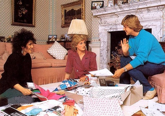 A rare private picture of Princess Diana with her designers David and Elizabeth Emanuel, taken inside her apartment's living room at Kensigton Palace, on 1985. David & Elizabeth Emanuel were the first designers ever that Diana worked with after her marriage. They first met her when she was engaged to the Prince of Wales, on 1981. She asked them to design her wedding dress, and since then, they became one of her favorite designers.