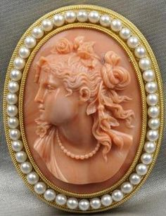 High Karat Gold, Coral Cameo And Cultured Pearl Brooch, The Cameo Depicting A Maiden With Flowing Hair And Flowers, Cultured Pearl Border, And Fine Braided Gold Frame