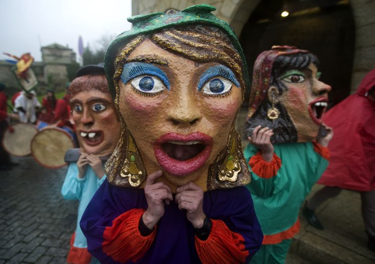 "Mask-wearing revelers make their way to the Carnival parade in Barcelos, northern Portugal, Sunday, March 2, 2014. Giant puppets and big heads, ""Cabecudos"" and ""Gigantones"" in Portuguese, are basic ingredients of northern pilgrimages, made with a wire frame and wood, coated paper and cloth, covered with plaster and glue and paint. (Photo by Paulo Duarte/AP Photo)"