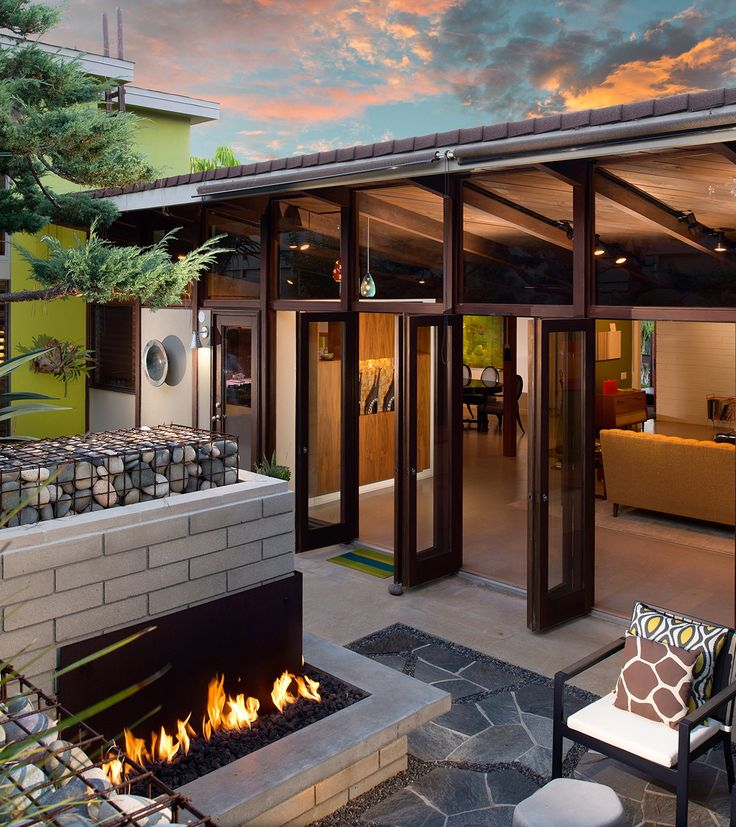 This unique home is a seamless integration of interior/exterior space, with glass walls that open to a gorgeous rock fireplace and patio
