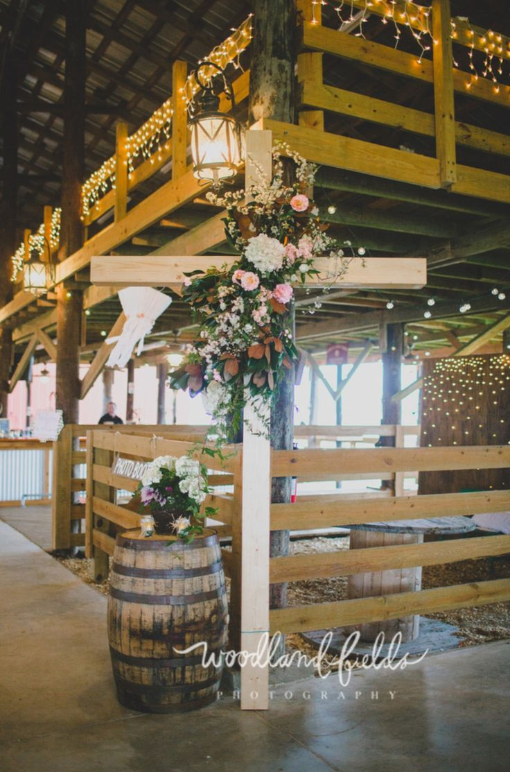 the ceremony took place inside the barn. the altar was adorned with a wooden cross built by the brides father and was dressed with magnolia branches, white blossom branches, white hydrangea, pink roses, peach stock, white wax flower, and jasmine trails