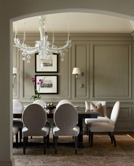 Add a bit of whimsy to a traditional room.... ~chose a playful chandelier to balance the traditional elements in this dining room. The soft rug, panel moulding and formal dining chairs feel less structured when paired with the statement lighting.