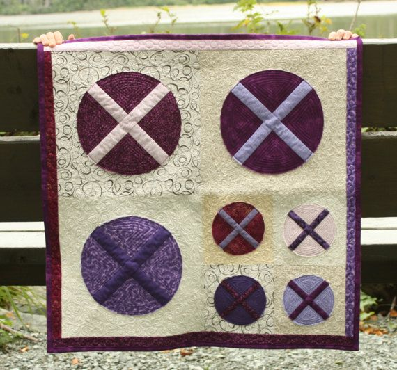 """The X Marks the Spot mini quilt (26"""" x 26"""") will make a great wall hanging or table topper. It is beautifully machine quilted and includes the many shades of purple will delight any purple-lover!"""