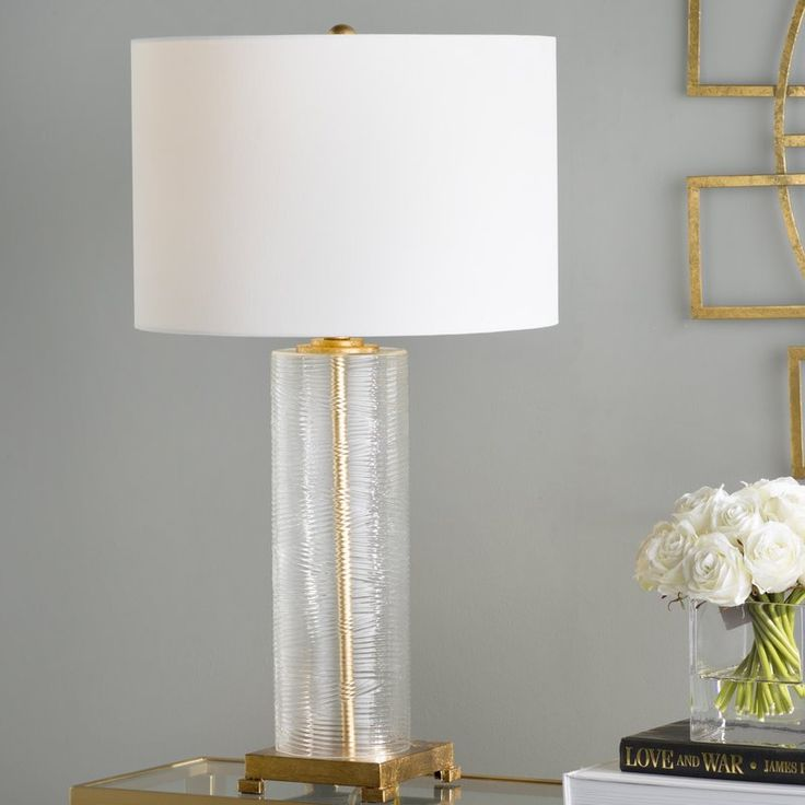 <p>Add a touch of simple sophistication to your home with this must-have lamp. Whether you want to liven up an understated space or just cast a warm glow, this lamp is a must-have accent. The textured glass base and white lamp shade bring a touch of timeless elegance to this design, while the gold leaf finished accents add a pop of glam. </p><p>Try setting this chic table lamp on a golden console in the entryway to welcome guests in glamorous style. Then pull up metalli...