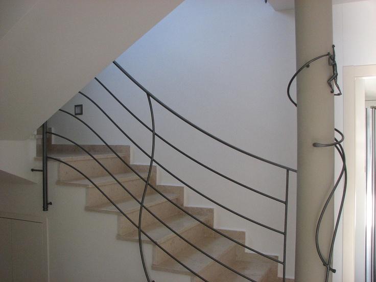מעקה מתכת לגרם מדרגות. המעקה מעוצב בצורה פיסולית, המחמיאה לקו העולה של המדרגות