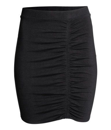 Black. Short, fitted jersey skirt with an elasticated waist and gathered seam at the front.