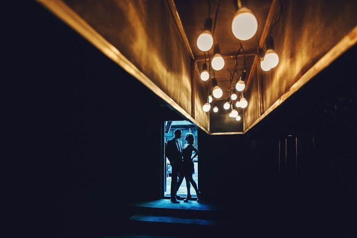 Николай Злобин (nikolaizlobin). Ракурс, геометрия, силуэт. Цветовой контраст, контраст темного на светлом, ритм, линейная перспектива. Общий план. Камера находиться на уровне головы жениха и невесты. Освещение смещенная, искусственного с естественным.