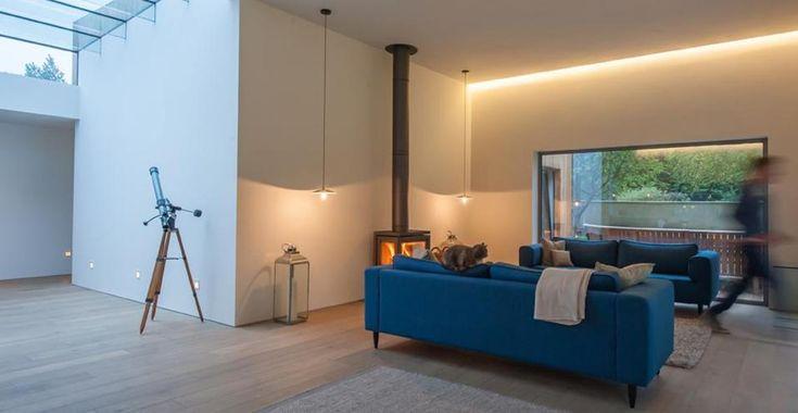 Casa di campagna eco nel cuore della campagna inglese. Il lucernario posto al centro dell'abitazione permette il passaggio di luce e aria naturale. L'angolo relax è vivacizzato da due divani blu cobalto davanti alla stufa in ghisa.