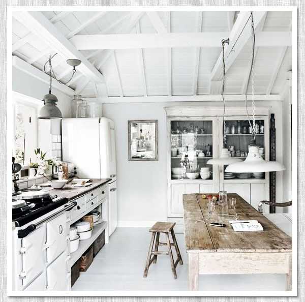 "Kitchen in a tiny fishing village of Mousehole, Cornwall. (Dylan Thomas called it ""the loveliest village in England""). Owned by photographer Paul Massey, the interiors feature his trademark mix of rustic furniture in shades of gray, greige, and white casually arranged in a series of pristine white-painted spaces."