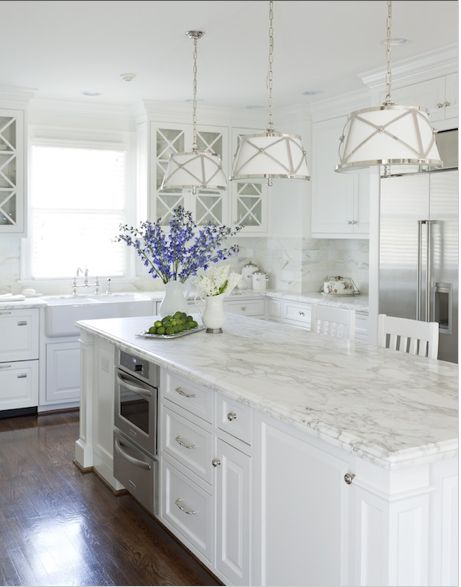 love the marble counter tops and the wood floor with this white kitchen